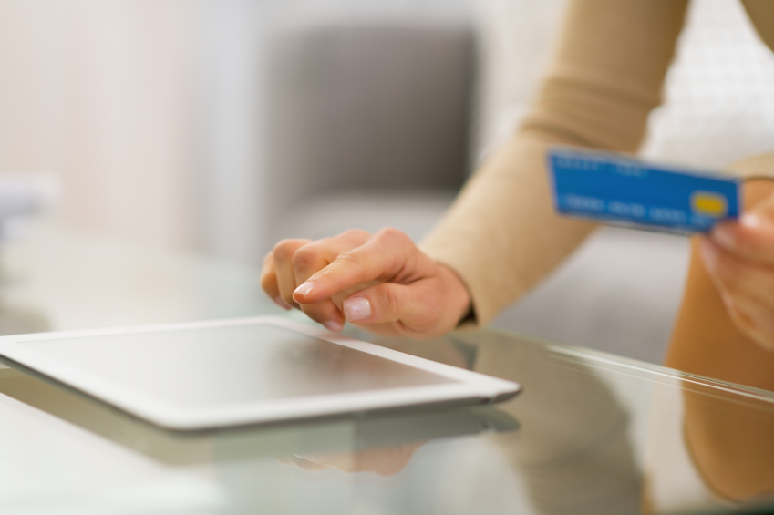 Closeup on young woman with credit card using tablet pc